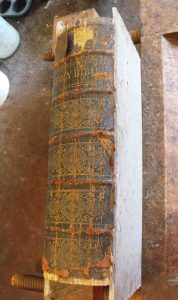 The text block is clamped into a press prior to removing the original spine.