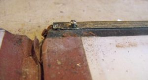 This Bible having brass edging, the tiny nails holding the edging in place are prised out.